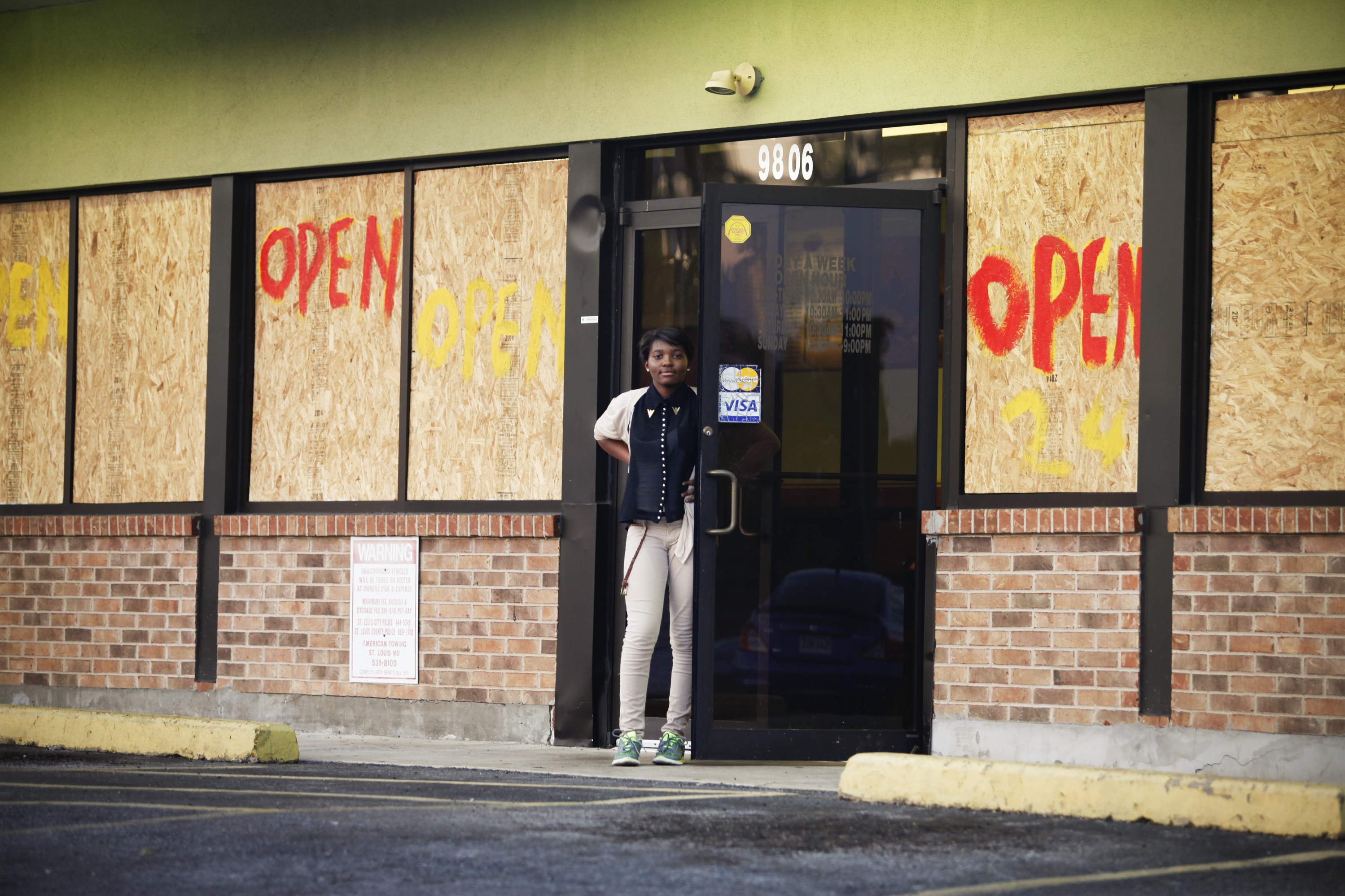 A woman stands before a restaurant on West Florissant Avenue where rioting took place earlier this week. Most of the stores on this stretch are boarded up -- some after they were damaged by looters, and some as a precaution -- even as many remain open for business.