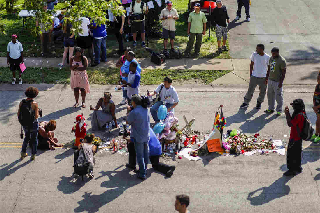 Residents and media near a memorial where Michael Brown was shot on Aug. 9, on Canfield Drive. Many of the people who weren't carrying protest signs were carrying roses.
