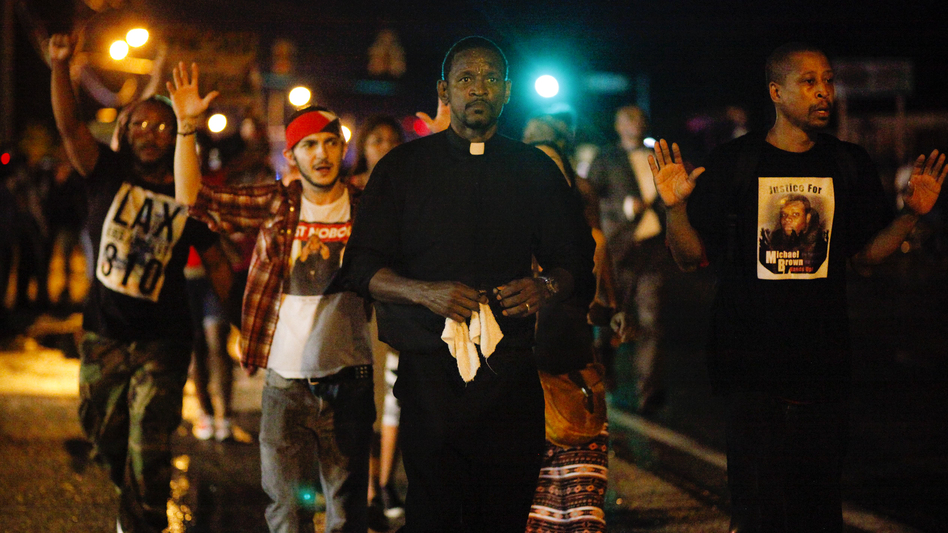 A clergyman leads demonstrators protesting the shooting death of Michael Brown down West Florissant Avenue in Ferguson, Mo., on Wednesday. A large contingent of clergy helped keep the mood calm after days of unrest. (Eric Kayne for NPR)