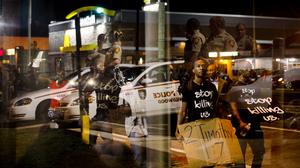 Law enforcement officers are reflected in a window as demonstrators walk past a bus stop in Ferguson.