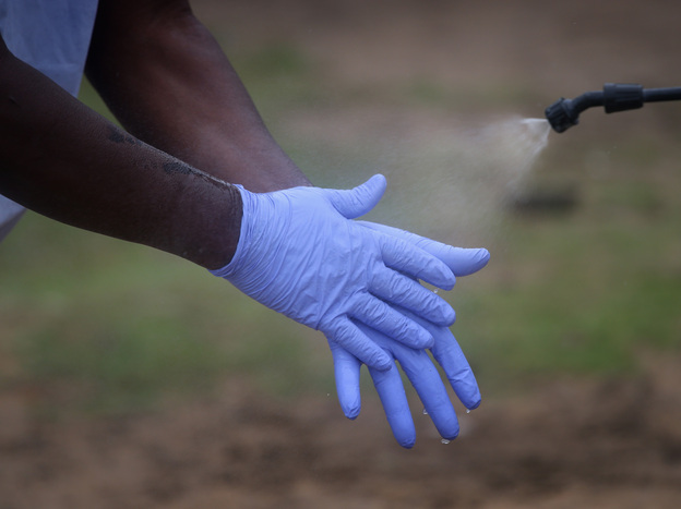 Protective equipment is in short supply. Here, a Liberian burial team carefully disinfects its gloves before disposing of them.