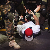 Police arrest a demonstrator protesting the killing of teenager Michael Brown in Ferguson, Mo.