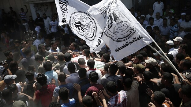 Hamas supporters carry the body of one of three Hamas senior commanders killed Thursday by an airstrike in the Gaza Strip. (AFP/Getty Images)