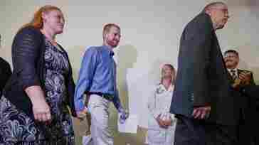 Ebola virus survivor Dr. Kent Brantly (center) and his wife, Amber (left), walk at a news conference at Emory University Hospital in Atlanta Thursday. Brantly and aid worker Nancy Writebol were discharged from the hospital less than a month after they contracted Ebola while treat