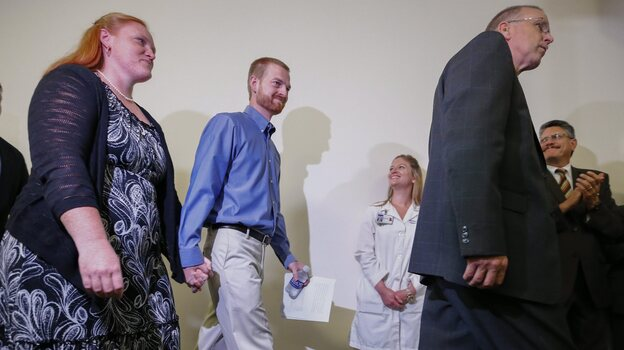 Ebola virus survivor Dr. Kent Brantly (center) and his wife, Amber (left), walk at a news conference at Emory University Hospital in Atlanta Thursday. Brantly and aid worker Nancy Writebol were discharged from the hospital less than a month after they contracted Ebola while treating patients in Liberia. (EPA/LANDOV)