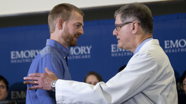 Dr. Bruce Ribner, medical director of Emory University Hospital's infectious disease unit, embraces Dr. Kent Brantly (left) who was treated with an experimental Ebola medicine and released from the Atlanta hospital Thursday.