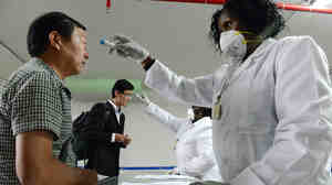 Kenyan health officials take the temperature of passengers arriving at Nairobi's airport.