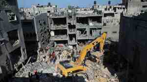 Palestinian emergency personnel dig through the rubble of a building destroyed by an Israeli military strike in Rafah in the southern Gaza Strip on Thursday. Hamas announced that three of its senior military commanders were killed in a predawn Israeli airstrike.