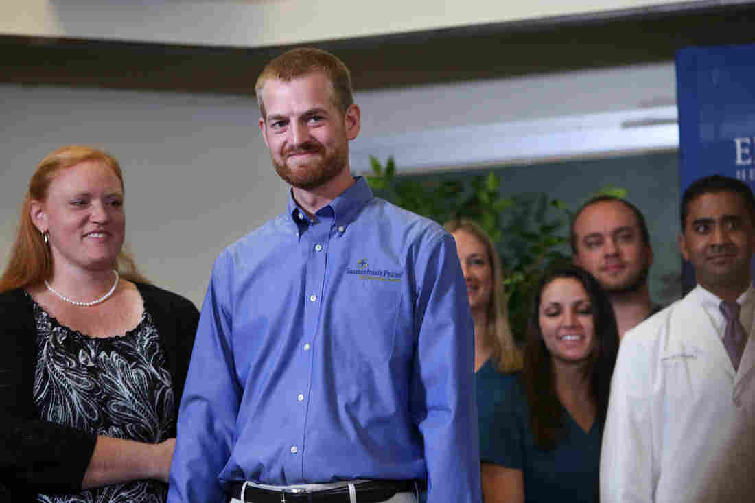 Dr. Kent Brantly (center) announces his recovery from Ebola, with his wife, Amber Brantly (left), during a press conference at Emory Univ