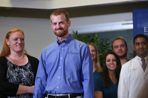Dr. Kent Brantly (center) announces his recovery from Ebola, with his wife, Amber Brantly (left), during a press conference at Emory University Hospital Thursday in Atlanta. Brantly got sick at the end of July.