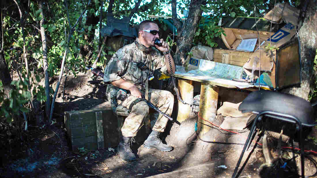 A Ukrainian soldier speaks with a fellow soldier on a portable radio transmitter in their military camp near Luhansk on Wednesday.