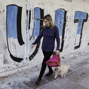 """A woman in Buenos Aires walks with her dog past a mural that reads """"Vultures"""" in Spanish. The mural is a reference to the dispute between the Argentine government and U.S. hedge funds."""