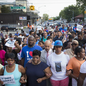 Eric Garner, an unarmed black man, died on July 17 after being placed in a chokehold by police. His death sparked numerous protests, including a march scheduled for this Saturday. Here, Garner's sister Ellisha Flagg (center) leads demonstrators on a march toward the 120th Precinct on July 22, following a vigil demanding justice for her brother.