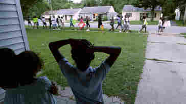 Children watch from their home in Ferguson, Mo., on Wednesday as people march to the police station to protest the shooting of Michael Brown. After more than a week of protests, riots and looting in the St. Louis suburb, the delayed school year is set to start Monday.