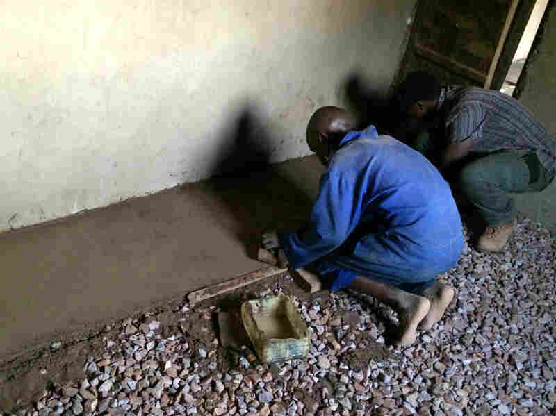 Gravel helps keep the floor level and prevents moisture from seeping up. The floor installers are Jean Pierre (left), a mason, and Daniel Shenyi, operations manager for EarthEnable.