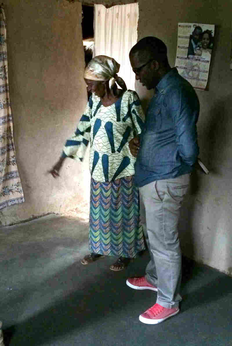 Emerence Mukakayijuka, a 72-year-old Rwandan grandmother, shows her new earthen floor to a visitor. Living without dirt floors for the first time, she marveled at the lack of dust in her home.