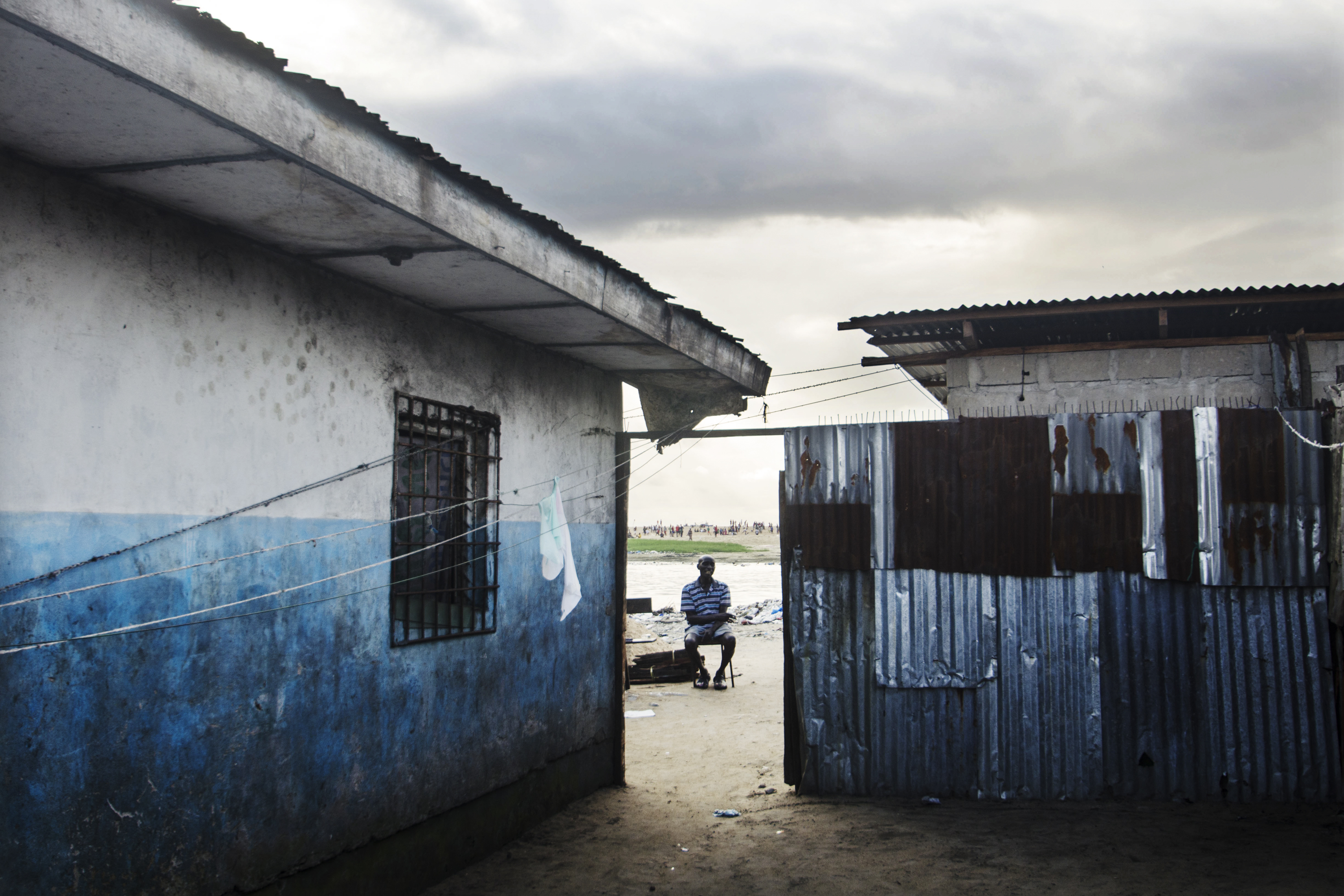 A resident takes in the view from this Liberian slum.