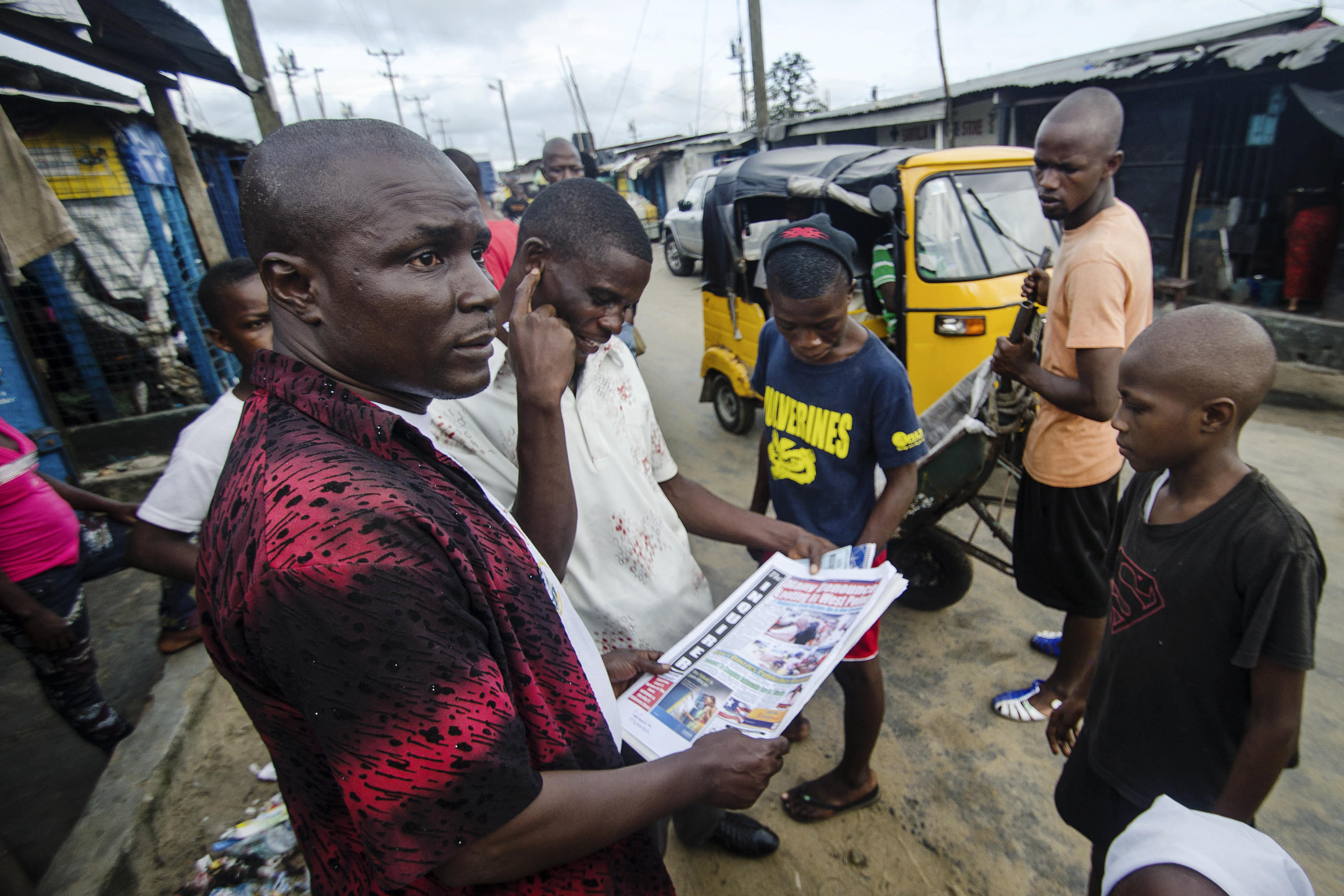 Residents gather on the main road to read newspaper headlines about Ebola.