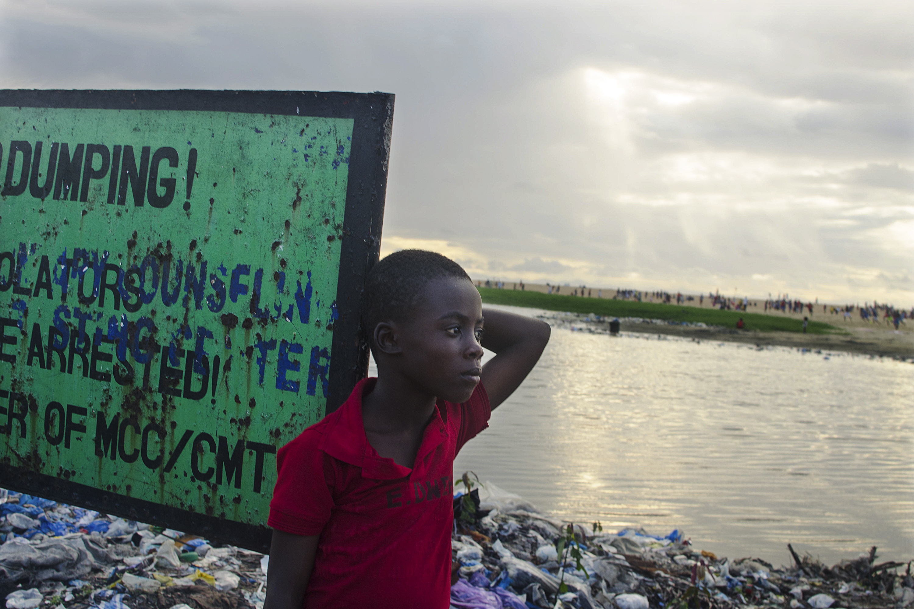 """Prince, a West Point resident, stands by a garbage dump near a sign that says """"No dumping."""""""