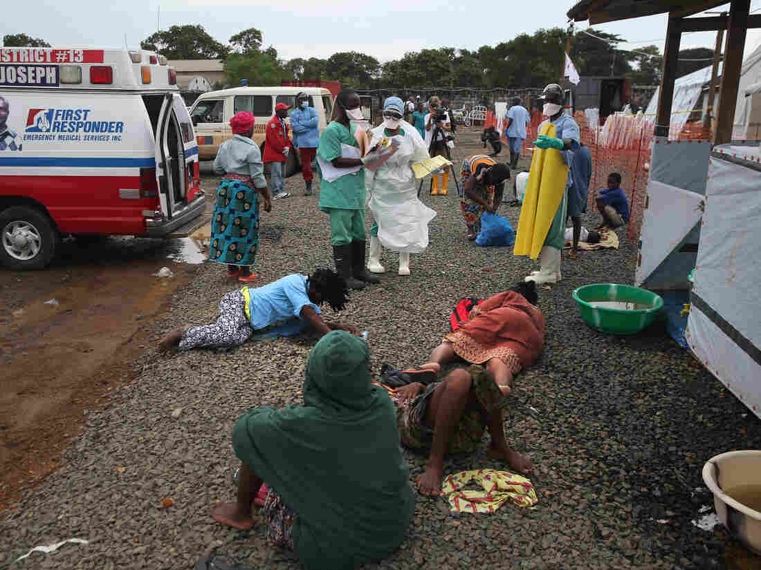 After arriving by ambulance, people with suspected Ebola virus lie on the ground before being admitted to the Doctors Without Borders Ebola treatment center in Monrovia, Liberia, last week. The 120 beds in the center were filled almost immediately.