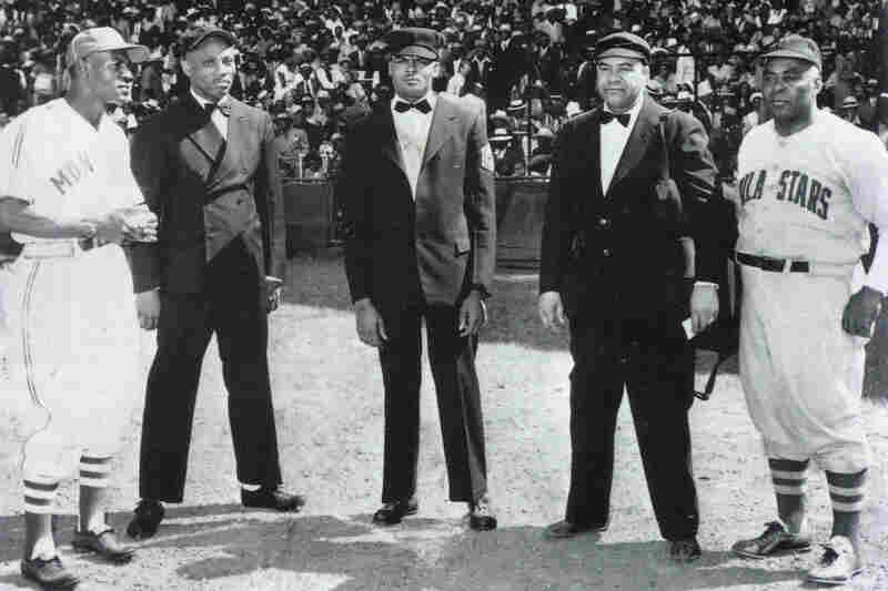 Motley (center) on Opening Day at Blues Stadium in Kansas City in 1949. With him are, from left, Monarchs manager Buck O'Neil, Sylvester Vaughn, Frank Duncan and Philly Stars manager Oscar Charleston.