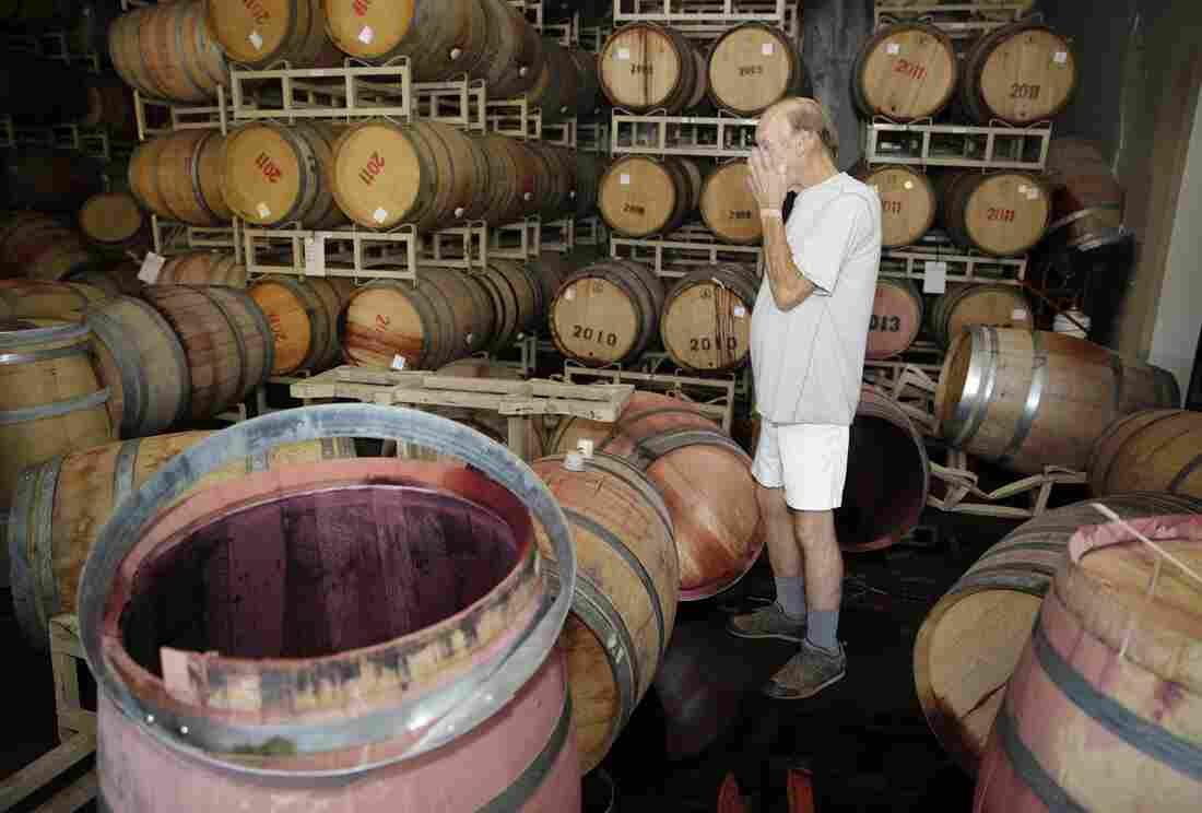 Winemaker Tom Montgomery stands in wine and reacts to seeing damage following an earthquake at the B.R. Cohn Winery barrel storage facility on Sunday in Napa Valley.