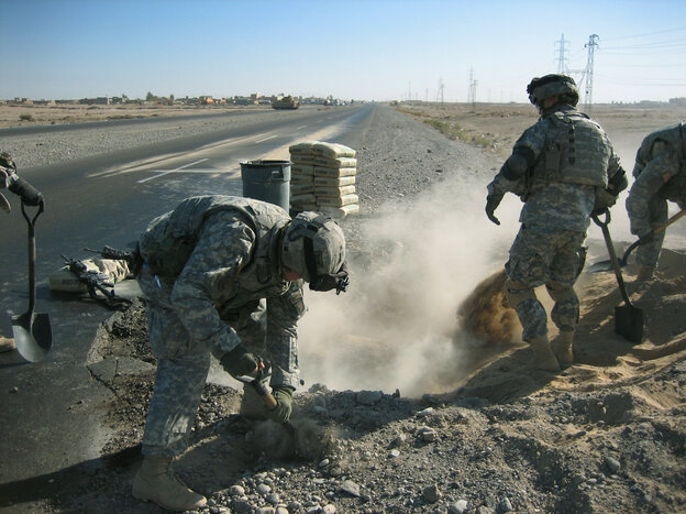 Soldiers fill a hole left by an explosion on a road outside Beiji, Iraq, in 2005. In his debut novel, Michael Pitre follows a group of Marines doing similar work on Iraq's highways.