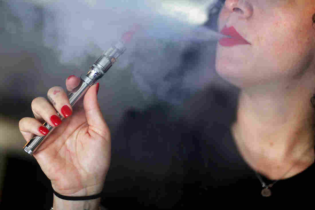 A woman smokes an electronic cigarette at a store in Miami.