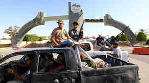 Islamist fighters in the Libya Dawn coalition guard the entrance of the Tripoli International Airport on Sunday. After days of battles, they captured it from forces aligned with rogue general Khalifa Hifter.