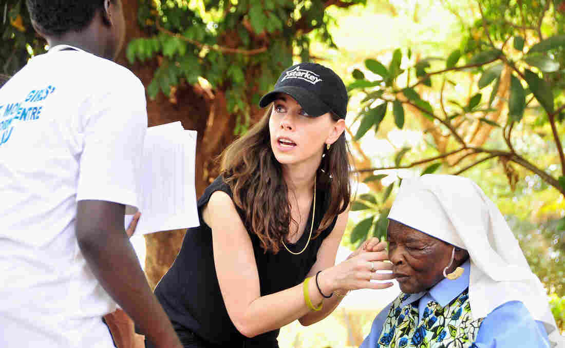 Barbara Bush helps a nun to fit on a hearing device during a 2012 event in Gulu, Uganda. She says was interested in architecture as a college student but became a global health activist after visiting East Africa with
