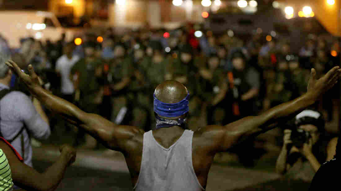 A demonstrator raises his arms before police officers move in to arrest him on Aug. 19 in Ferguson, Mo.