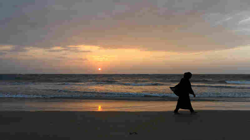A Sri Lankan beachgoer walks during sunset in Colombo on Jan. 30, 2014.
