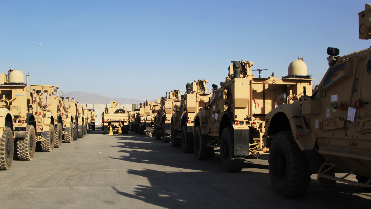 Armored vehicles, known as M-ATVs, are lined up on the tarmac at Bagram Airfield. They will be flown out to the Persian Gulf on cargo planes and then shipped back to the US.