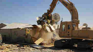 A construction excavator demolishes a so-called B-Hut at the huge Bagram Air Field norht of Kabul. The military used the structures as bunks and offices during the 13-year war but is tearing them down as most of the military prepares to leave by year's end.