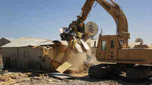 A construction excavator demolishes a B-hut at the huge Bagram Air Field north of Kabul. The military used the structures as bunks and offices during the 13-year war but is tearing them down as most of the military prepares to leave by year's end.