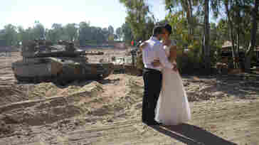 Israeli couple, Noga and Moshiko Siho, kiss after they have their wedding photos taken in an army staging area on the Israeli Gaza border, near Kibbutz Yad Mordechai, Israel on Wednesday.