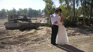 An Israeli couple, Noga and Moshiko Siho, kiss after they have their wedding photos taken Wednesday in an army staging area on the Israel-Gaza border, near Kibbutz Yad Mordechai, Israel.