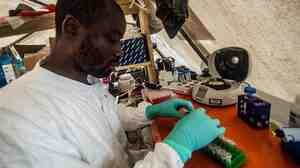 A technician tests fluid samples from Ebola-infected patients at a field lab, run by Doctors Without Borders, in Kailahun, Sierra Leone.