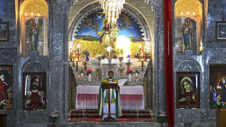 Friar Gabriel Tooma leads a service at the Chaldean Church of the Virgin Mary of the Harvest, in Al-Qoush on June 15. At the time, the Christian village in northern Iraq was taking in those fleeing violence in the nearby city of Mosul. Now the village itself is largely deserted.
