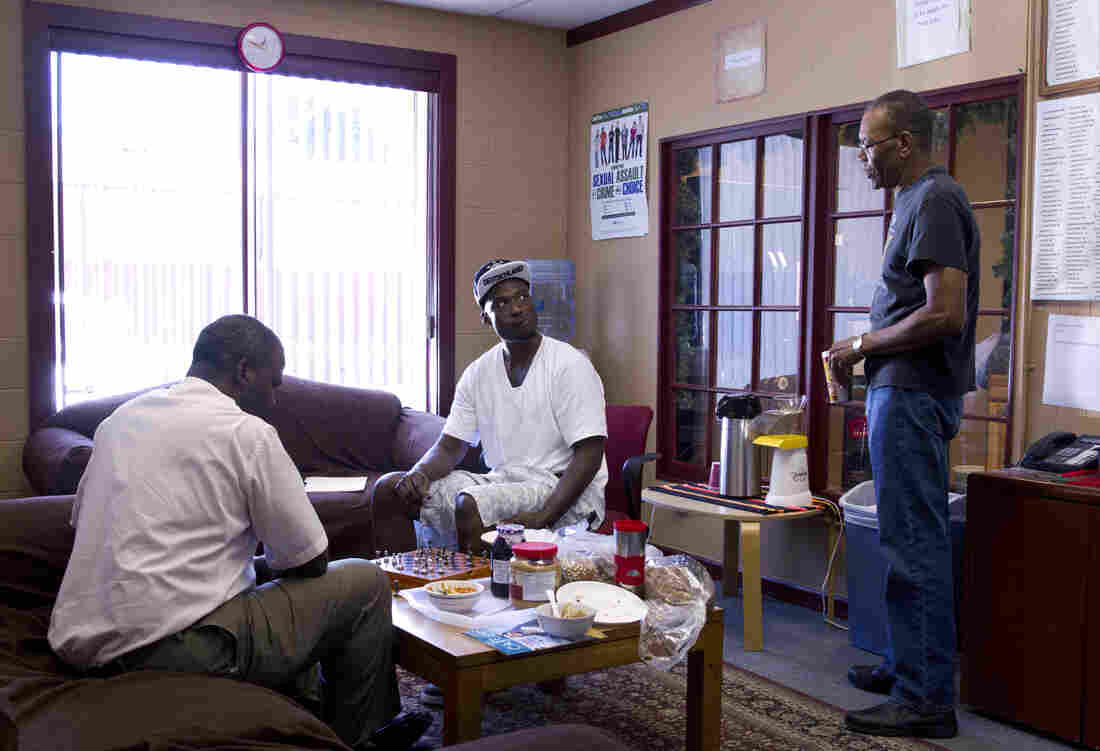 David Lee Robinson Jr. (left), a volunteer facilitator, plays chess with Michael Ward at a prison re-entry program site, while Felton Howard, a navigator with the program, looks on. Ward spent more than eight years in the state prison system before his release in 2012.
