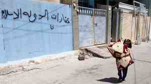 An Iraqi child walks next an empty house of a Christian family in Mosul on Aug. 8. The Arabic writing on the wall