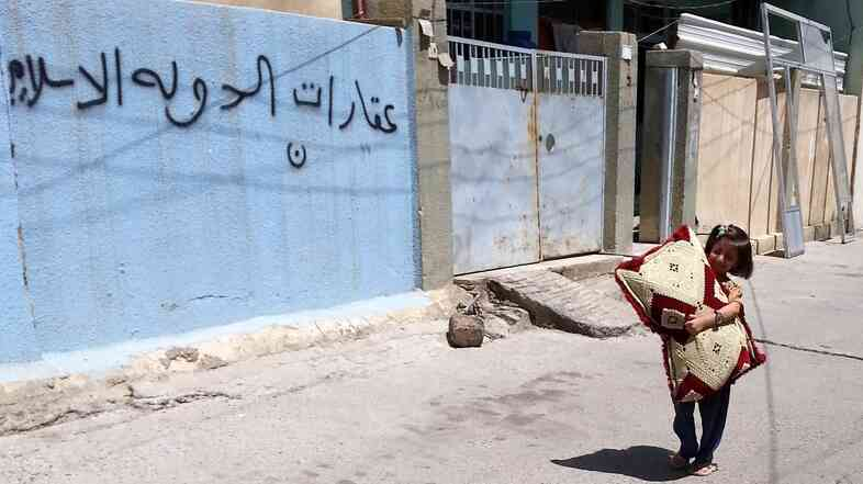 "An Iraqi child walks next an empty house of a Christian family in Mosul on Aug. 8. The Arabic writing on the wall reads ""Real Estate of the Islamic State."" The extremist group took control of Mosul, Iraq's second largest city, in June."