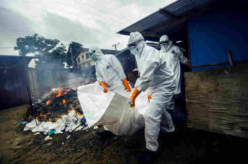 A burial team collects a body from the Ebola unit at JFK hospital in Monrovia. Protective suits are burned in the background — a precautionary measure to prevent the spread of the virus.
