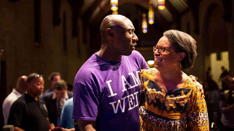 """The Rev. Willis Johnson (left), pastor of Wellspring Church in Ferguson, speaks to the Rev. Michele Shumake-Keller after the panel discussion in Ferguson, Mo., on Thursday. Johnson said he hoped the event would be a step to healing a """"community in trauma."""""""