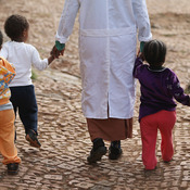 A woman walks with children at an orphanage in Addis Ababa, Ethiopia. Policymakers have long called for orphans to be taken out of institutions and placed with foster families, but one study from Duke University is challenging that notion.
