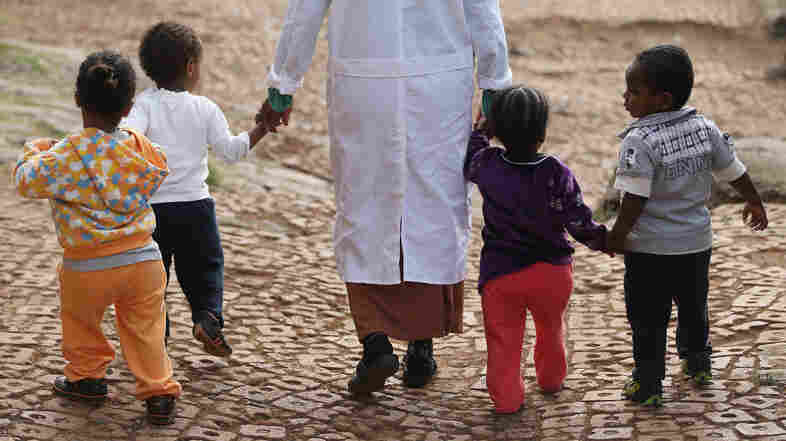 A woman walks with orphans at an orphanage in Addis Ababa, Ethiopia. Policy makers have long called for orphanages to be taken out of institutions and placed foster families, but one study from Duke University is challenging that notion.