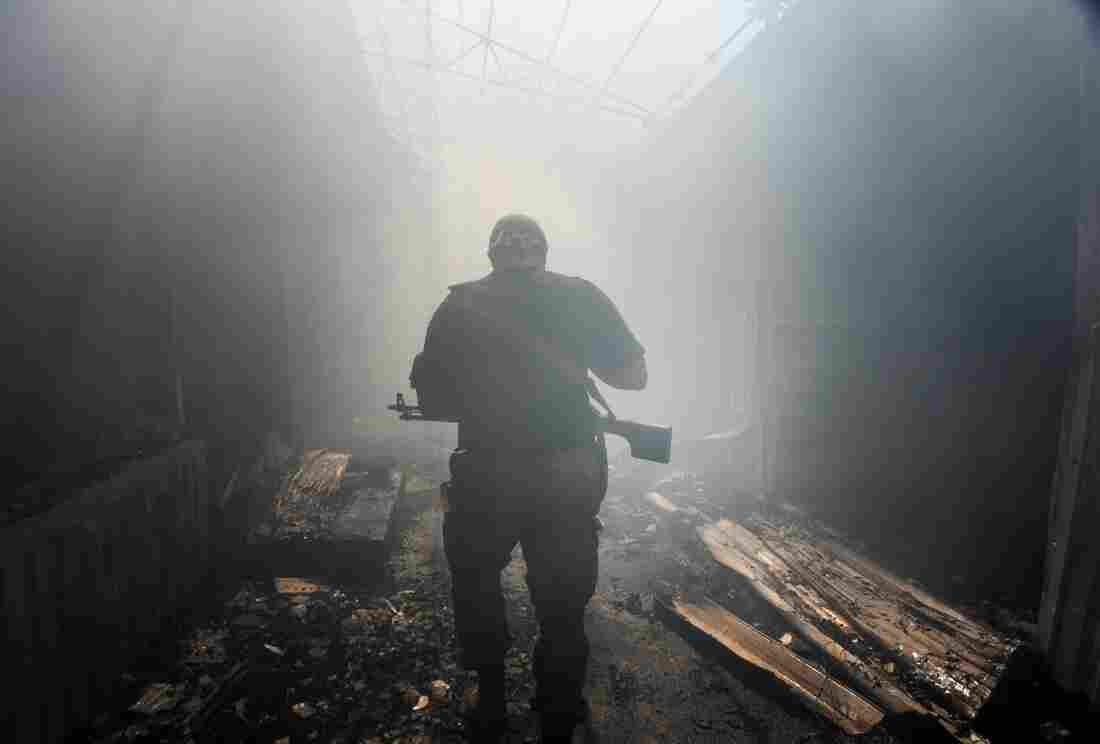 A pro-Russian rebel walks in a passage at a local market damaged by shelling in Petrovskiy district in the eastern Ukrainian town of Donetsk.