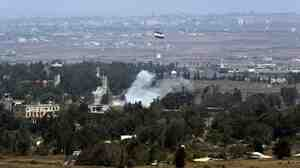 Smoke rises near a Syrian flag hoisted up a flagpole as a result of the fighting between Syrian rebels and the Syrian Army over the control of Quneitra crossing, on Saturday. The area is where  dozens of U.N. peacekeepers had been under siege by Nusra Front fighters.