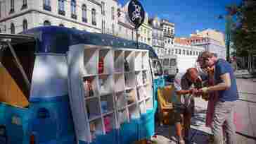 Francisco Antolin, the driver and co-founder of Tell A Story, speaks to a couple of Danish tourists who purchased some books from his mobile bookstore. The converted van travels around Lisbon and sells translations of Portuguese literature.