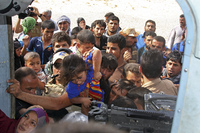 In Amerli, people try to board an Iraqi Army helicopter aid flight bringing in supplies to the town on Saturday. The town, which includes some 20,000 Shiite Turkmen, has been surrounded by Sunni Islamic State fighters for two months.